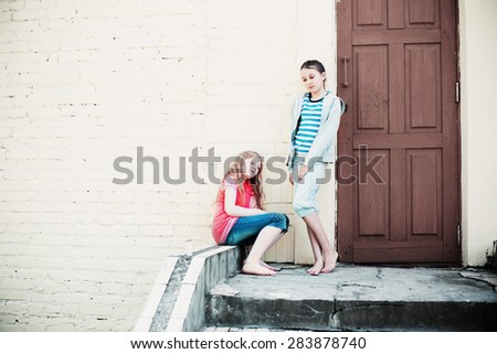two sad girls on background wall - stock photo