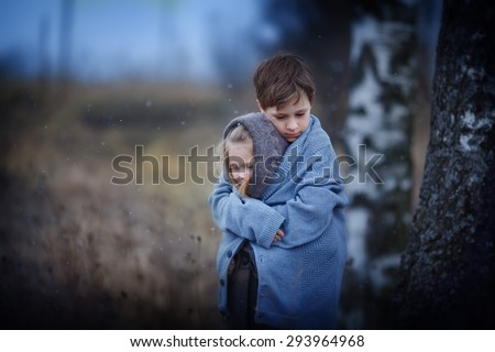 Two sad little embracing children in the field on a cool spring evening. Kids in the country - stock photo