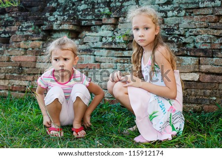 two sad little girls on the background of an old brick wall - stock photo