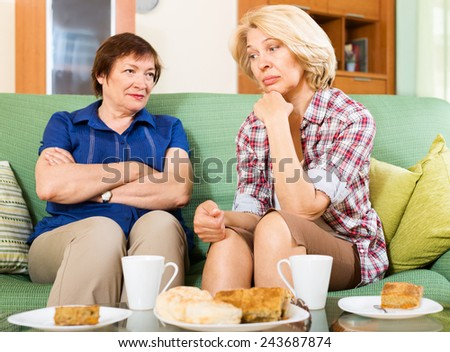 Two sad mature women  discussing problems  - stock photo