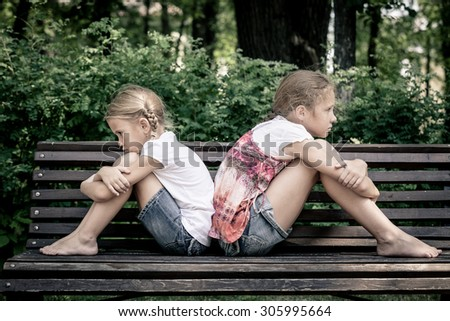 two sad sister sitting on the bench in park at the day time - stock photo