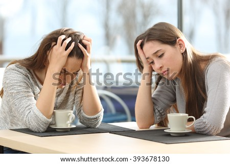 Two sad women worried in a coffee shop with a window in the background - stock photo