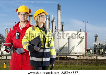 Two safety specialists monitoring the perimeter of a petrochemical refinary, using electroncial devices, such as cb radios and tablets