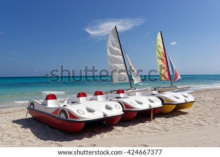 Two sail boats and three pedal boats on a tropical beach with blue sky and water background