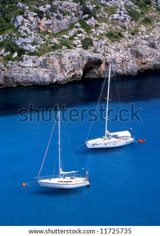 Two sail boats in the bay of Paleokastritsa on the greek island of Corfu - stock photo