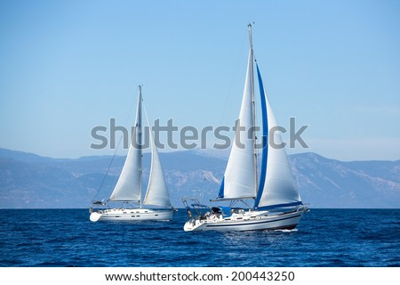 Two sailboats on peaceful still waters in a harbor. - stock photo