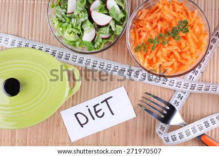 Two salads. To lose weight, weight loss, healthy food. Radish salad and greens. Grated carrots. Pan, two bowls of salad and a measuring tape on the table. Sliced vegetables.