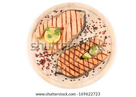 Two salmon steaks on platter. Isolated on a white background.