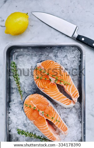 Two salmon steaks with thyme in a pan with ice - stock photo