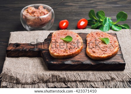 Two sandwiches on loaf of bread with meat pate decorated with salad leaves, glass bowl with meat pate, served on the Board at a brown wooden surface - stock photo