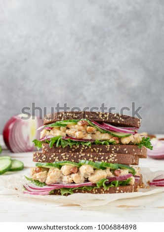 Two sandwiches with chicken, mushrooms, red onions, cucumber, lettuce and walnuts. Rustic style. Selective focus