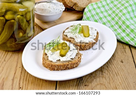 Two sandwiches with cream, pickles and dill, a napkin on wooden board