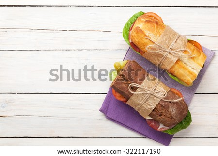 Two sandwiches with salad, ham, cheese and tomatoes on wooden table. Top view with copy space - stock photo
