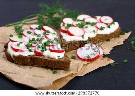 Two sandwiches with sour cream, onions and radishes and dill on a package on a isolated  black background - stock photo