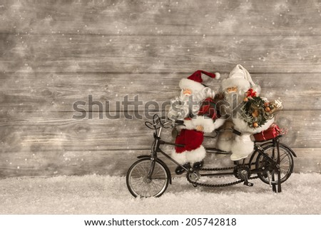 Two santa claus in hurry for buying christmas presents decorated on wooden background with snow in vintage style. - stock photo