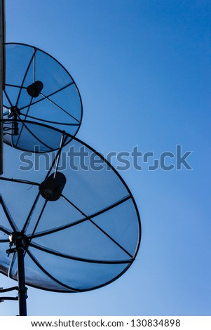 Two satellite dishes on blue sky