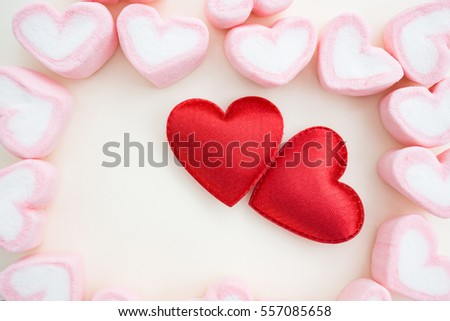 Two satin red hearts with pink heart marshmallows using as background valentine's day concept.