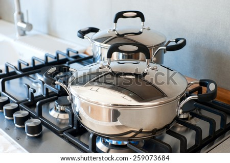 Two saucepans stainless steel on gas stove - stock photo