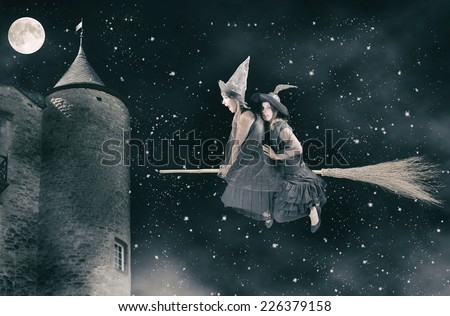 two scared witches flying on a broom. Black background with moon and stars - stock photo