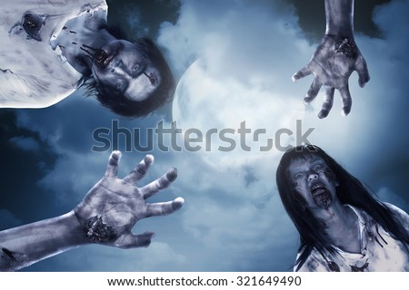 Two scary zombie with full moon background. Halloween concept - stock photo