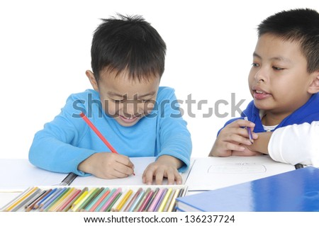 Two School boy sitting and writing in notebook - stock photo