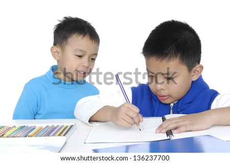 Two School boy sitting and writing in notebook. Isolated on white background - stock photo
