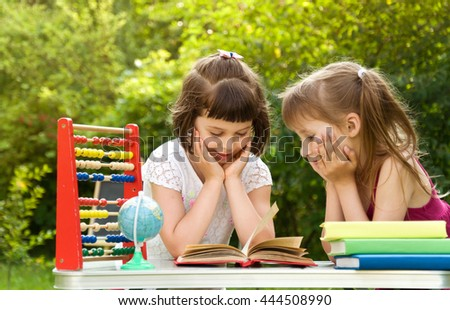 Two school girls are preparing a lesson in nature. They read books