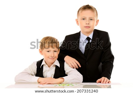 Two schoolboys do their lessons together at the table. Isolated over white.