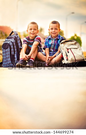 Two schoolboys taking a break on their way home. - stock photo