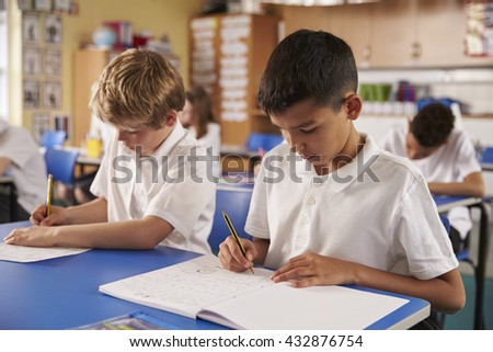 Two schoolboys working in a primary school class, close up - stock photo