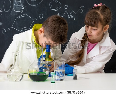 two schoolchildren in white gowns watching chemical experiment in lab