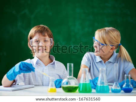 Two schoolchildren working with chemical liquids at lesson - stock photo