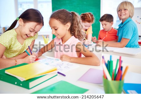 Two schoolgirls drawing in group on background of classmates