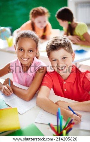 Two schoolkids looking at camera while drawing on background of little girls - stock photo