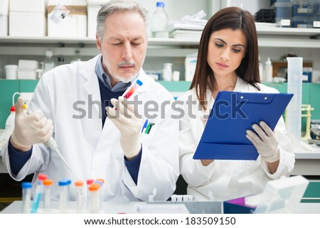 Two scientists at work in a laboratory - stock photo