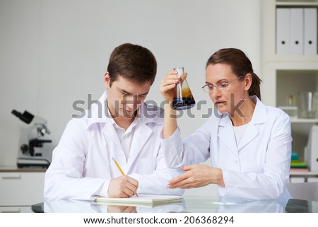 Two scientists making analysis of liquid oil in flask in laboratory - stock photo