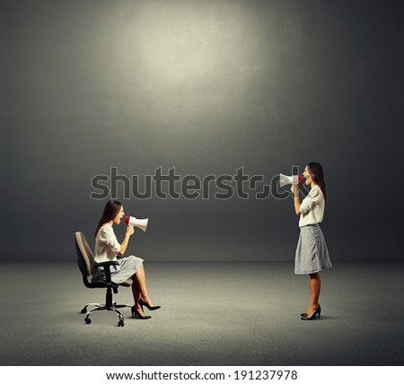 two screaming women with megaphone over dark background - stock photo