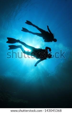 Two Scuba Divers silhouette against sun - stock photo