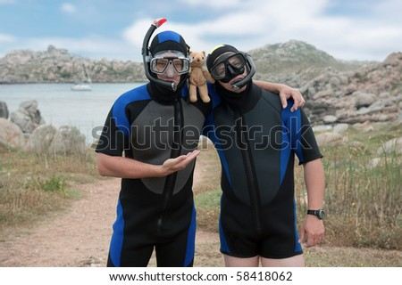 two scuba divers with teddy bear on island - stock photo