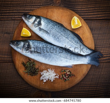 Two sea bass fish on cutting board