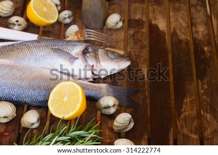 Two Seabass raw fish with shellfish and spices on wooden table  w - stock photo