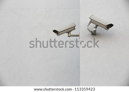 Two security camera�s on a wall.