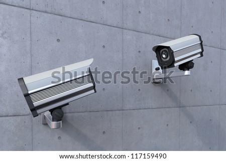 two security camera watching each other on concrete wall