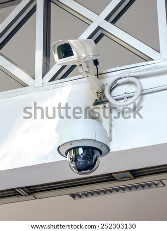 Two security cameras on a wall - stock photo