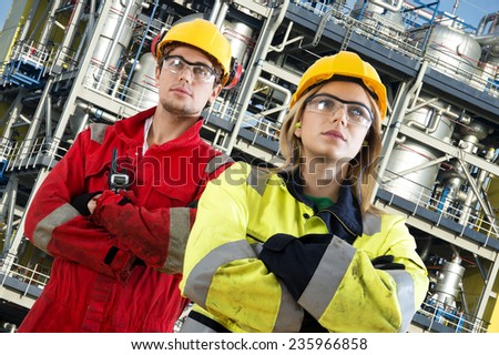 Two security engineers at their jobs, posing confidently in front of a large chemical installation with tanks, valves, tubes and safety structures - stock photo