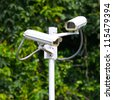 two security surveillance cameras near green forest - stock photo