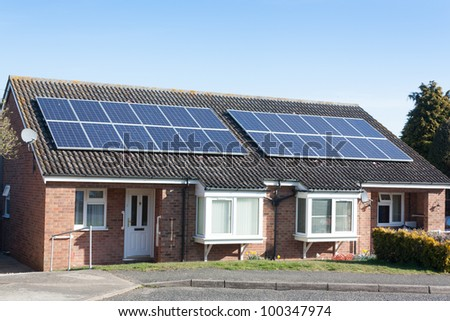 Two semi-detached bungalows both have solar panels on the roof. - stock photo