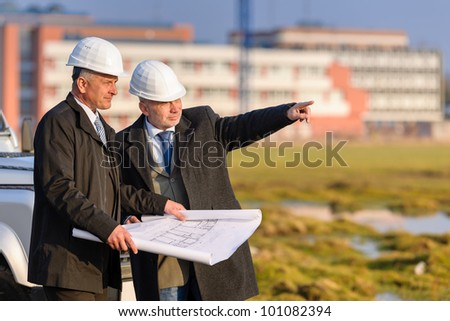 Two senior architect developers review plans at a construction site - stock photo