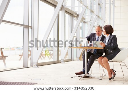 Two senior business colleagues at meeting in modern interior - stock photo