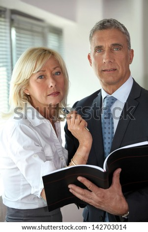 Two senior business workers discussing pensions - stock photo